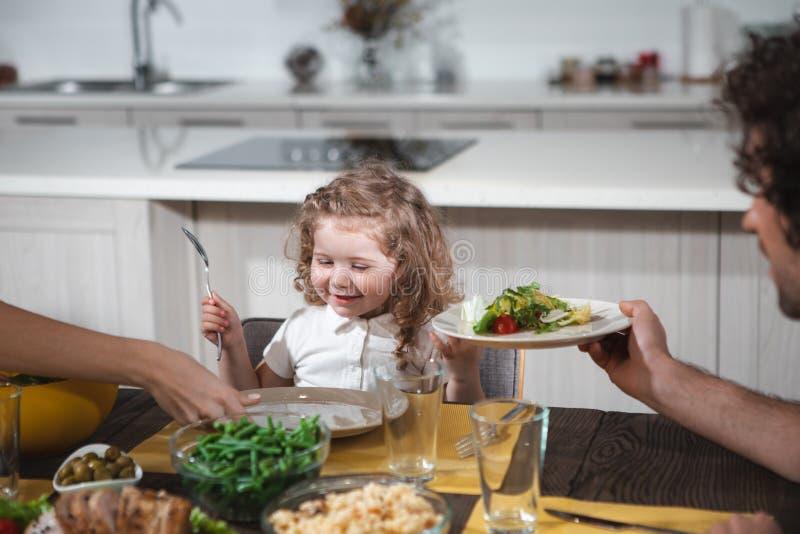 Blij meisje die salade samen met ouders eten stock afbeeldingen