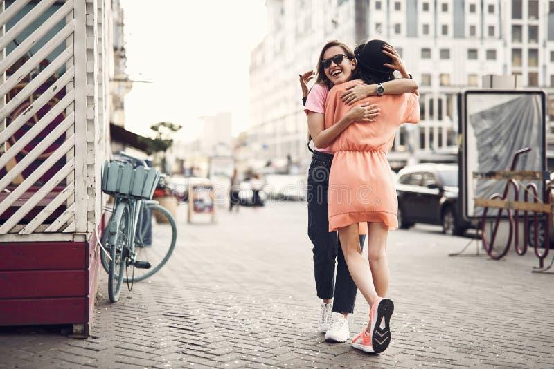 Blij meisje die vrouwelijke vriend koesteren royalty-vrije stock foto
