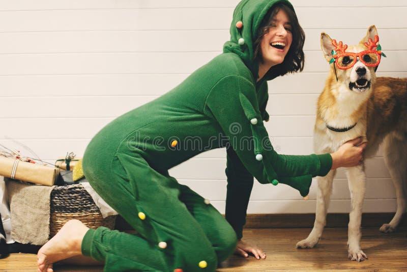 Blij meisje in feestelijke pajama met een hond in een kerstbril met hertenhoorns, op de vloer met kerstcadeaus in stock fotografie