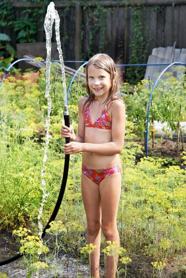 Blij meisje met tuinslang en water royalty-vrije stock foto's