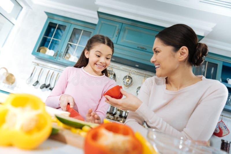 Blij meisjes glimlachende en hakkende groenten stock foto