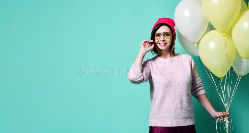 Blij model die pret hebben en met pastelkleurballon vieren stock foto