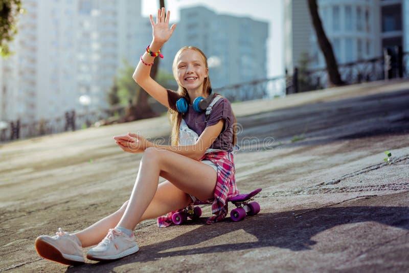 Blij modieus schoolmeisje die rechts haar golven royalty-vrije stock afbeelding