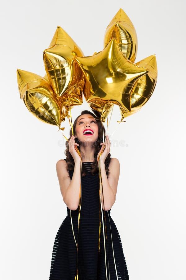 Blij mooi jong wijfje die omhoog op ster gevormde ballons kijken royalty-vrije stock afbeeldingen