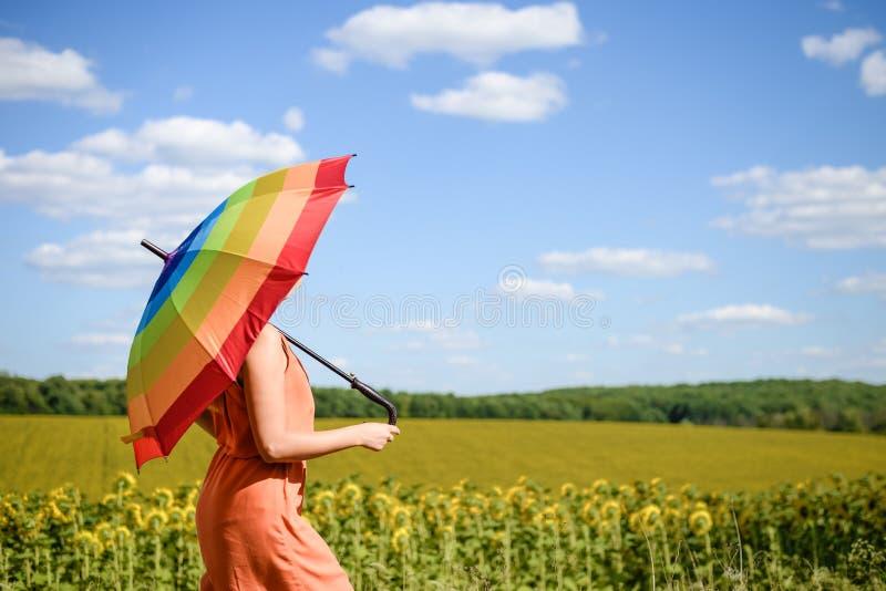 Blij mooi meisje die multicolored paraplu op zonnebloemgebied en de blauwe achtergrond van de wolkenhemel houden royalty-vrije stock foto