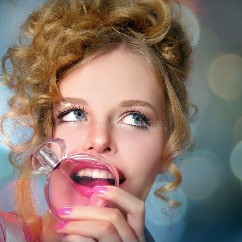 Blij mooi meisje met parfum in een hand stock fotografie