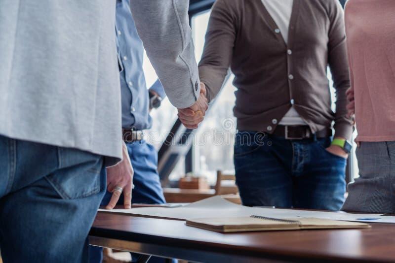 Blij om met u te werken! Jonge moderne mensen in slimme vrijetijdskleding het schudden handen en het glimlachen terwijl het werke stock fotografie