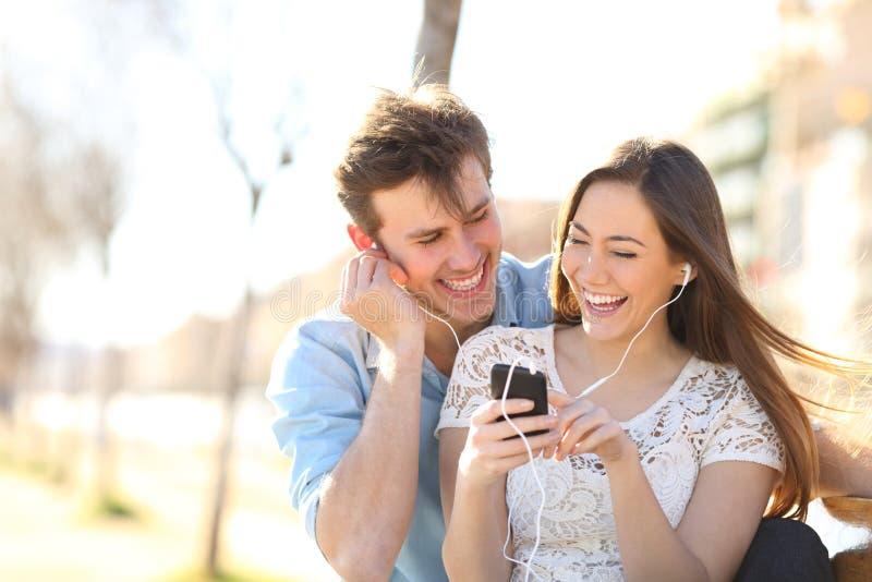Blij paar die aan muziek van een smartphone in een pak luisteren stock foto's