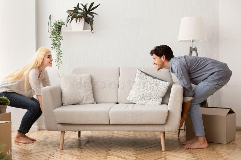 Blij Paar die Sofa While Moving Into New-Huis dragen royalty-vrije stock afbeelding