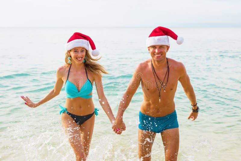 Blij paar in Kerstmanhoeden die op het strand lopen royalty-vrije stock foto's