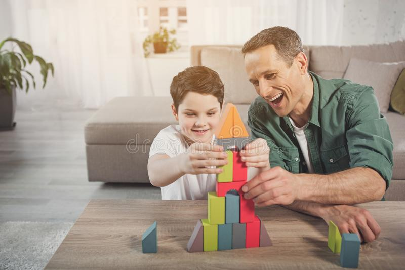 Blij papa en zoons de bouwstuk speelgoed huis royalty-vrije stock foto