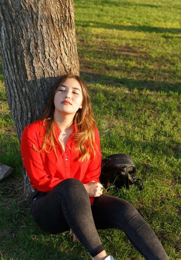 Blij positief Aziatisch meisje die van weekend in openlucht genieten Jonge vrouwenzitting op rode deken, die terug op boom, het h royalty-vrije stock afbeelding