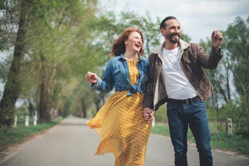 Blij rijp houdend van paar die langs parksteeg lopen stock foto's