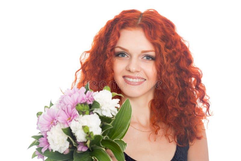 Blij rood haired meisje met bloemen stock fotografie