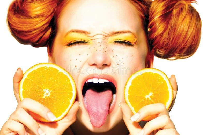 Blij tienermeisje met sappige sinaasappelen. Sproeten stock afbeeldingen