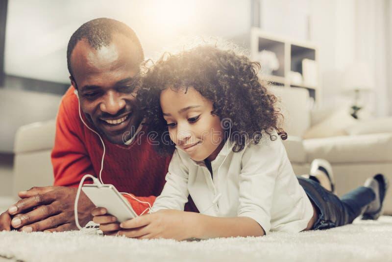Blij vader en jong geitje gebruikend mobiele telefoon met oortelefoons stock afbeelding
