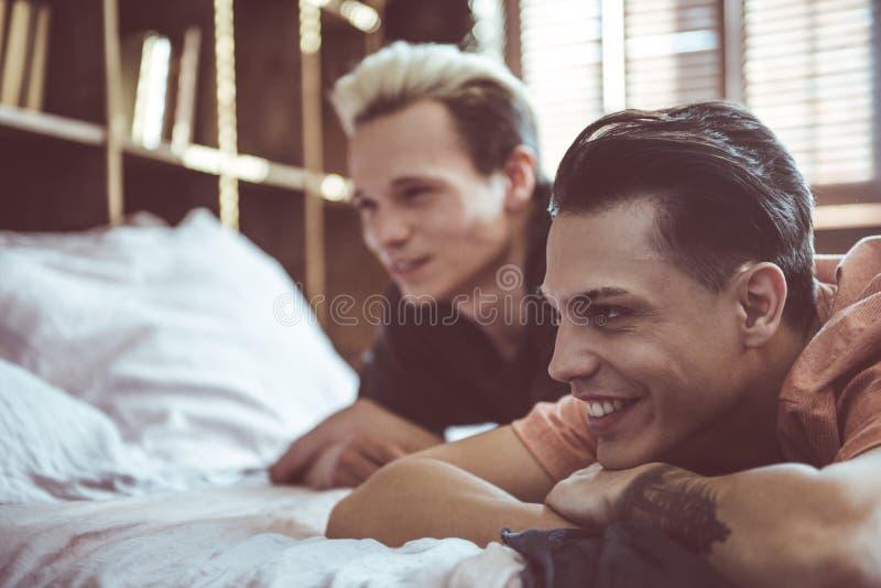 Blij vrolijk paar die samen thuis rusten stock fotografie