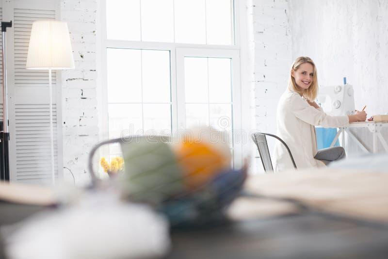 Blij vrouwelijk meer couturier het ontwerpen kledingstuk stock foto's
