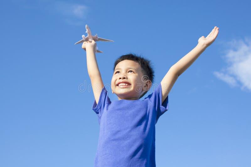 Blij weinig jongen die een stuk speelgoed met blauwe hemel houden royalty-vrije stock afbeeldingen