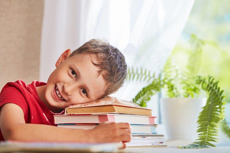 Blij weinig jongenszitting bij de lijst met potloden en handboeken Gelukkige kindleerling die thuiswerk doen bij de lijst royalty-vrije stock foto's