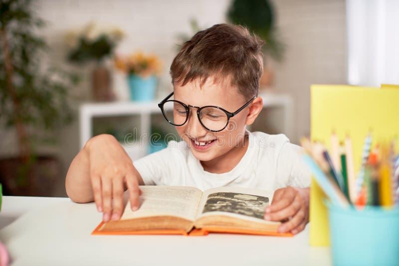 Blij weinig jongenszitting bij de lijst met potloden en handboeken Gelukkige kindleerling die thuiswerk doen bij de lijst stock foto's