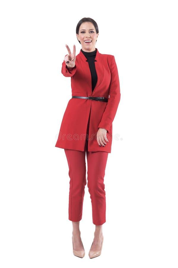 Blije aantrekkelijke bedrijfsvrouw in elegant rood kostuum die twee vingersoverwinning of het teken van de vredeshand tonen stock foto's