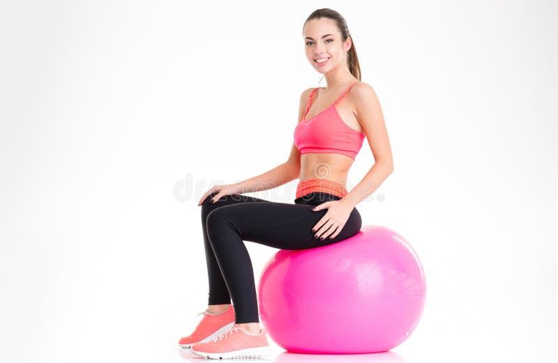 Blije aantrekkelijke jonge sportvrouwzitting op roze fitball stock foto