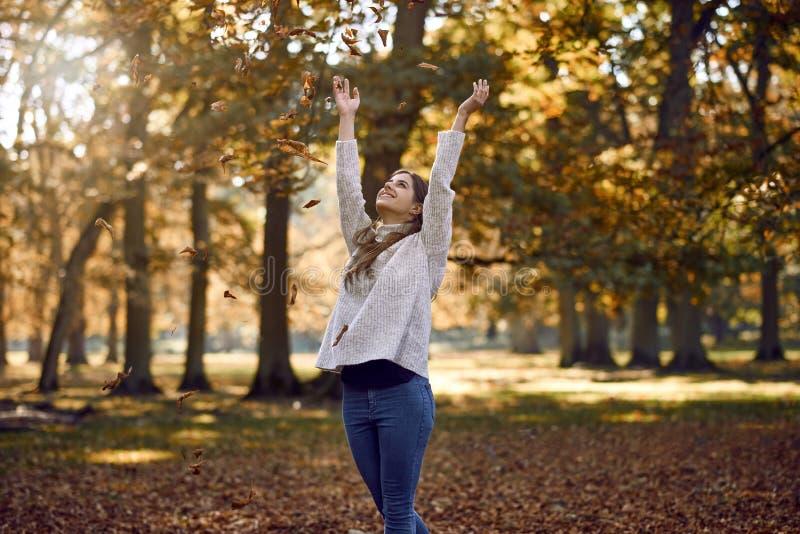 Blije aantrekkelijke jonge vrouw die de herfstbladeren werpen stock foto