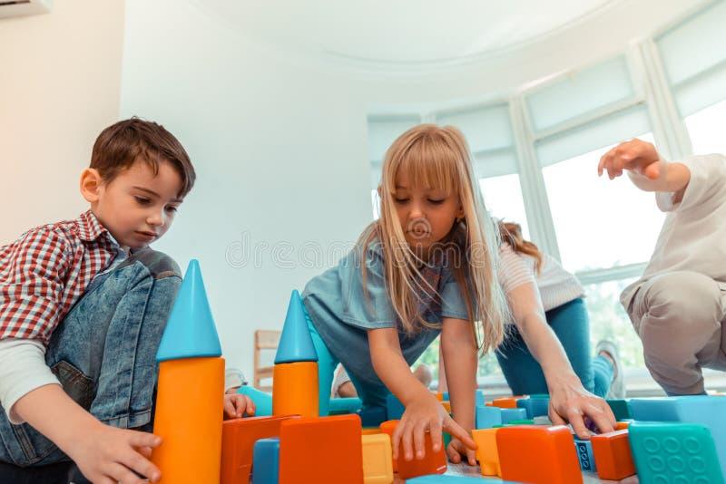 Blije aardige kinderen die een toren van speelgoed bouwen stock afbeeldingen
