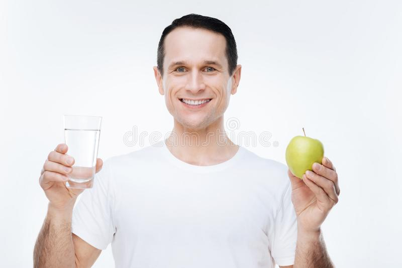 Blije aardige mens die een appel houden royalty-vrije stock afbeelding