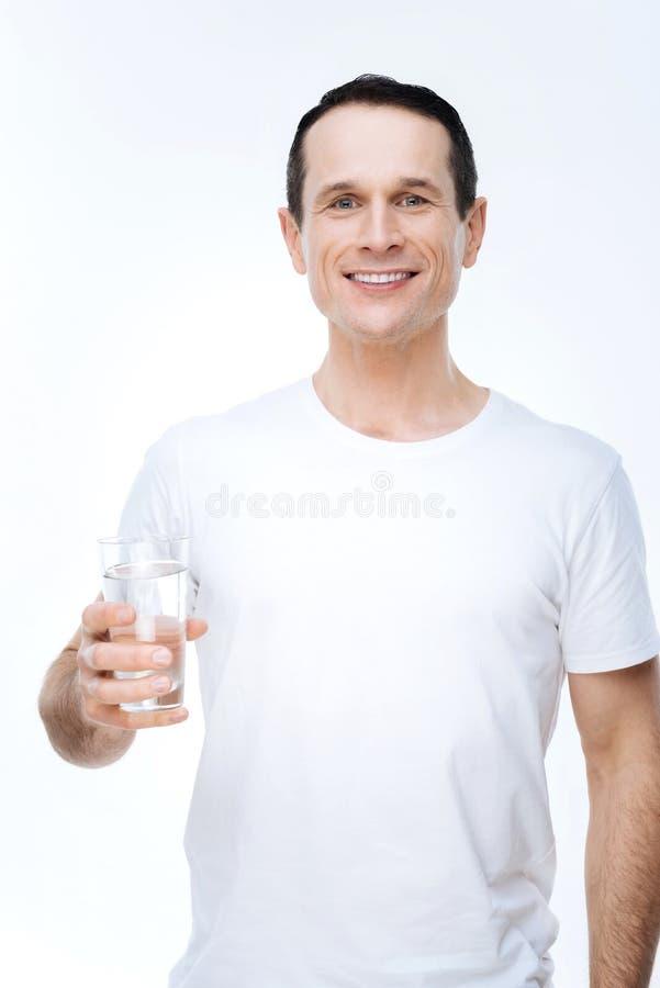 Blije aardige mens die een glas water houden royalty-vrije stock afbeeldingen
