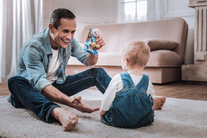 Blije aardige mens die een stuk speelgoed houden royalty-vrije stock foto