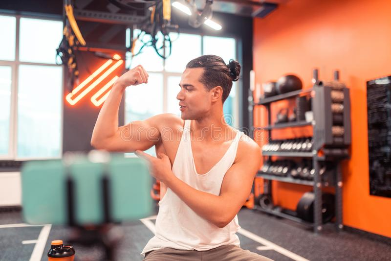 Blije aardige mens die zijn spieren bekijken stock foto