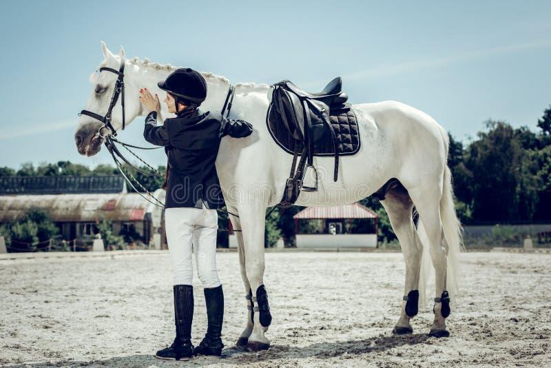 Blije aardige vrouw die een paard willen berijden stock foto