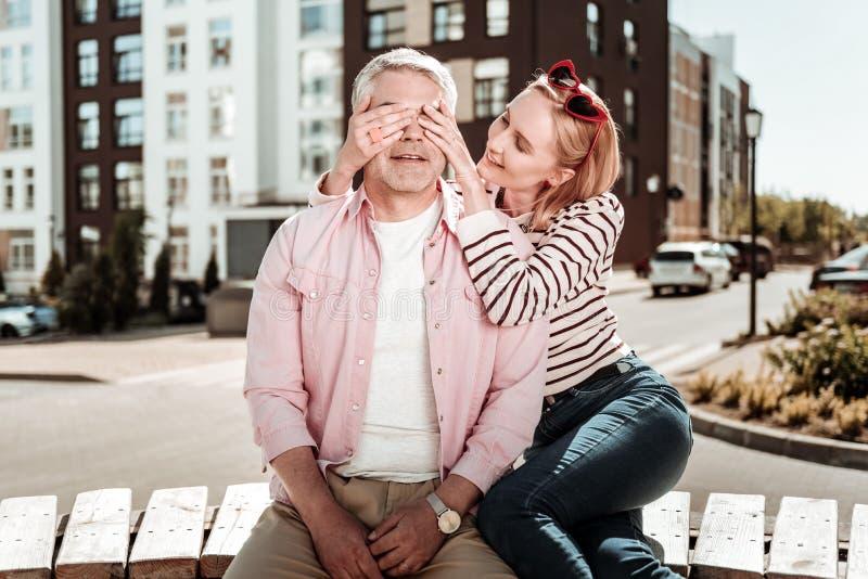 Blije aardige vrouw die haar echtgenotenogen behandelen stock foto