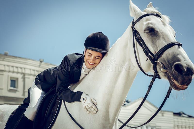 Blije aardige vrouw die haar liefde uitdrukken aan het paard stock foto
