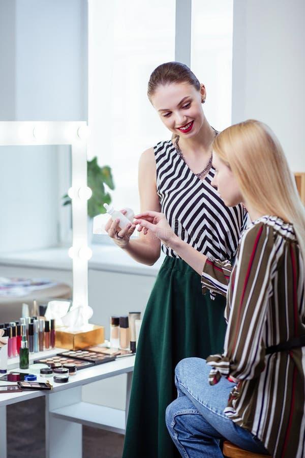 Blije aardige vrouw die sommige cosmetischee producten adviseren stock afbeeldingen