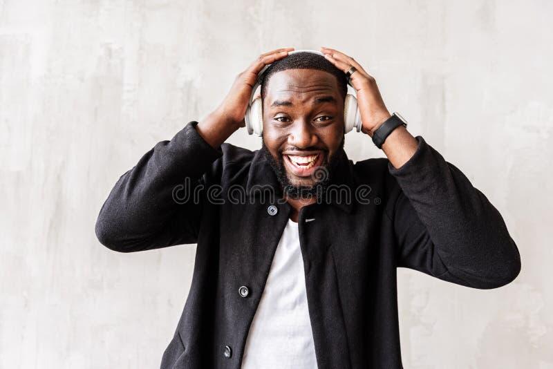 Blije Afrikaanse knappe kerel die genoegentijd het luisteren liederen op mp3 speler hebben stock foto's