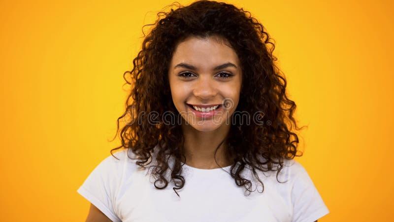 Blije Afrikaanse vrouw het glimlachen camera op oranje achtergrond, natuurlijke schoonheid, de jeugd stock fotografie