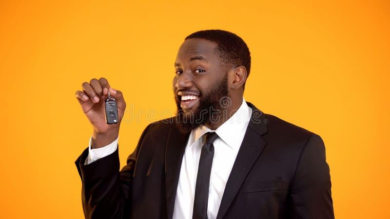 Blije Afro-Amerikaanse mens in kostuum die automobiele sleutels tonen, hurend auto, het huren stock foto