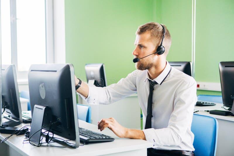 Blije agent die in een call centre met zijn hoofdtelefoon werken royalty-vrije stock fotografie