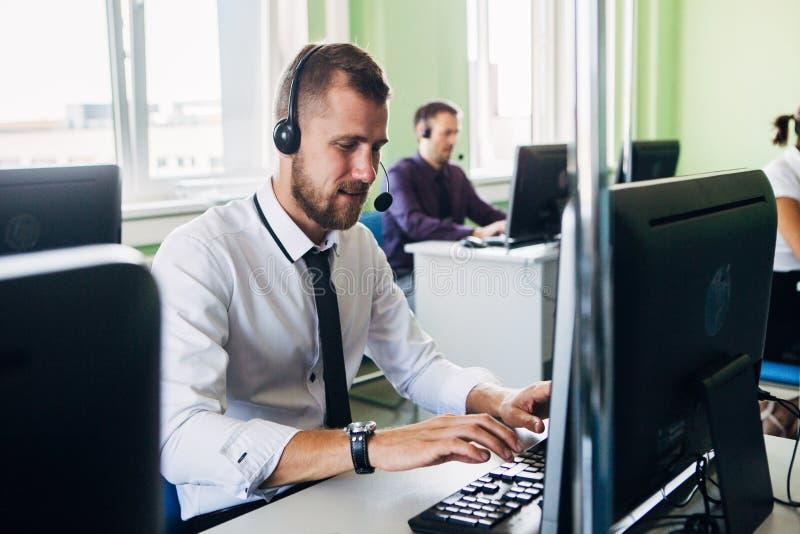 Blije agent die in een call centre met zijn hoofdtelefoon werken stock foto