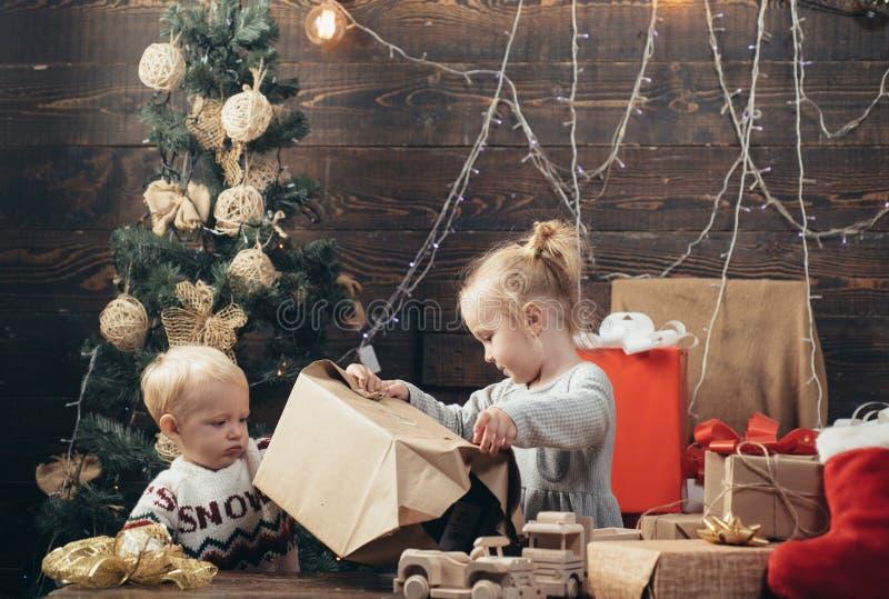 Blije baby die camera in Kerstmis thuis bekijken Vrolijk leuk kind die aanwezige Kerstmis openen Leuk weinig kind stock foto's