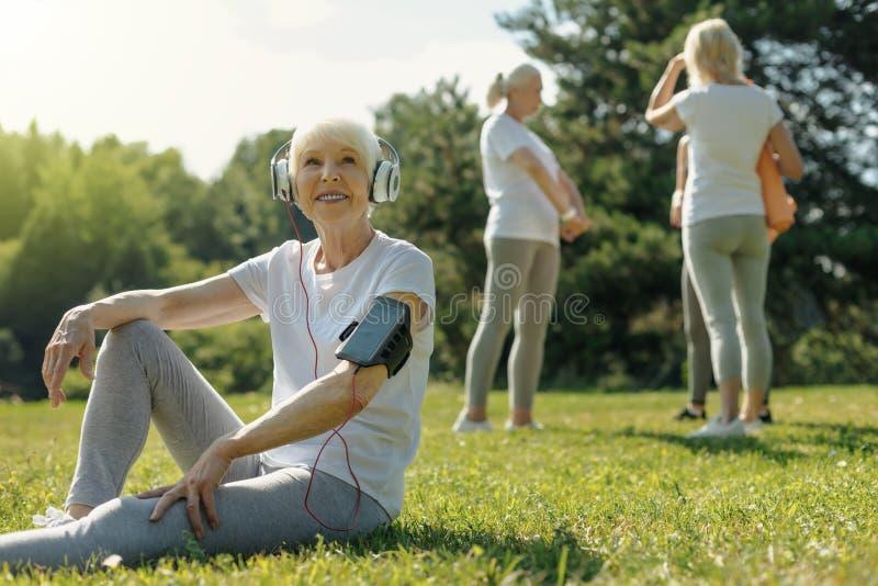Blije bejaarde dame die aan muziek na geschiktheid opleiding luisteren royalty-vrije stock fotografie
