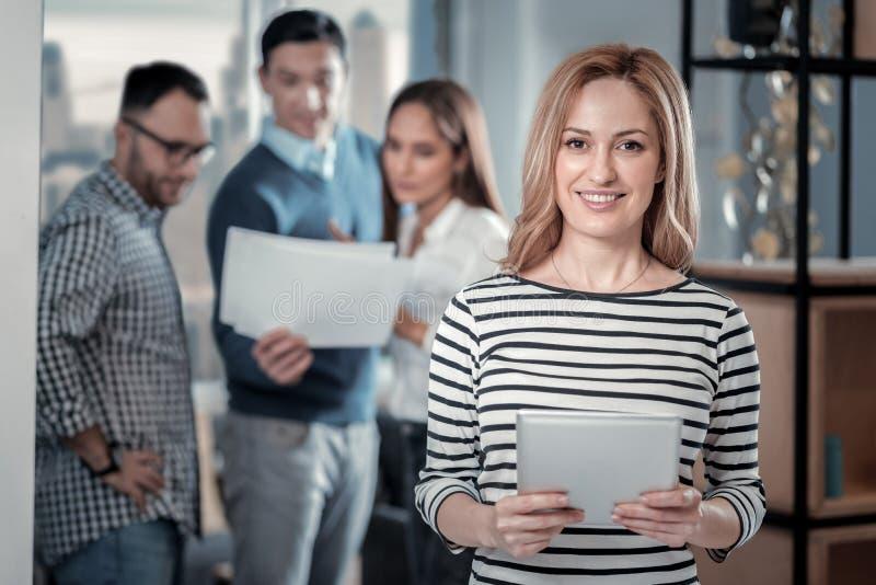 Blije blonde vrouw die zich met haar tablet bevinden stock afbeeldingen