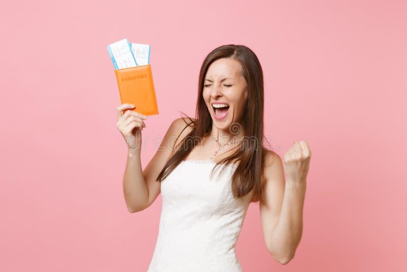 Blije bruidvrouw in witte huwelijkskleding die winnaargebaar doen, paspoort en instapkaartkaartje houden die, naar het buitenland royalty-vrije stock foto's