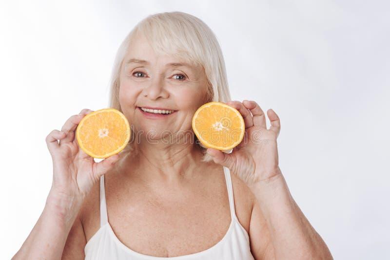 Blije charmante vrouw die de oranje helften houden royalty-vrije stock fotografie