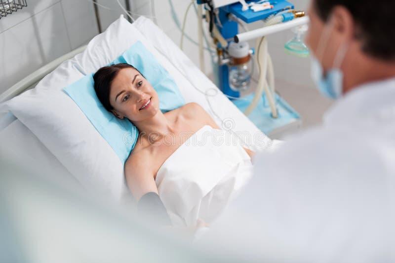 Blije dame luisterarts terwijl het liggen in het ziekenhuisbed stock fotografie