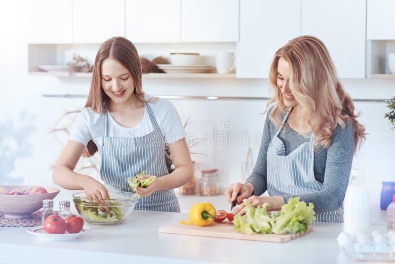 Blije dochter en moeder die gezond diner samen koken royalty-vrije stock afbeeldingen