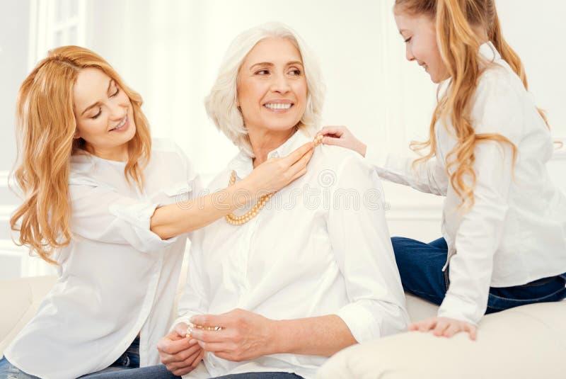 Blije drie generaties van vrouwen die omhoog zich thuis kleden stock foto
